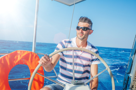 Young man sailing yacht. Holidays, people, travel