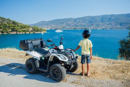 Little boy riding quad bike. Cute child on quadricycle. Motor cross sports on Greece island. Kids summer vacation activity. Reklamní fotografie