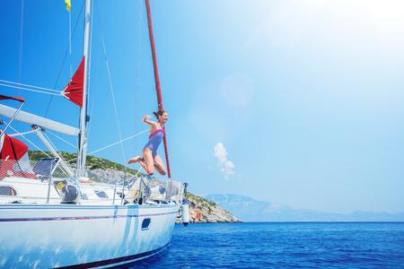 Chica salta en el mar del yate de vela en crucero de verano. Viaje de aventura, navegando con niños de vacaciones.