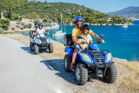 Family riding quad bike. Cute boy and his father on quadricycle. Motor cross sports on Greece island. Family summer vacation activity. Imagens