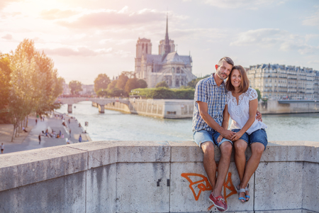 Happy couple hugging near Notre-Dame cathedral in Paris. Tourists enjoying their vacation in France. Romantic date or traveling couple concept Imagens