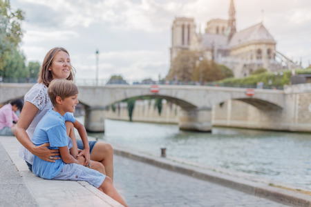 Happy mother and her son having fun near Notre-Dame cathedral in Paris. Tourists enjoying their vacation in France.