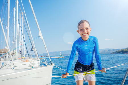 Little boy having fun on board of yacht on summer cruise. Travel adventure, yachting with child on family vacation. Stockfoto