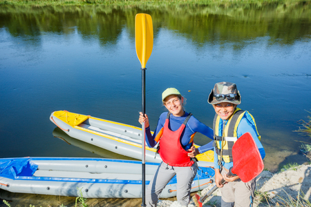 Happy kids kayaking on the river on a sunny day during summer vacation Stock Photo