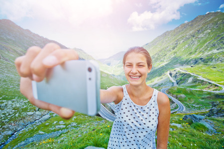 The girl takes a selfie photo of Transfagarasan mountain road. Romania.
