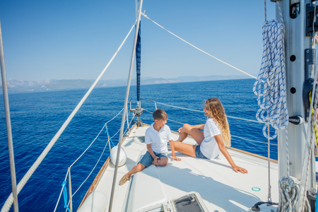 Boy with his sister on board of sailing yacht on summer cruise.