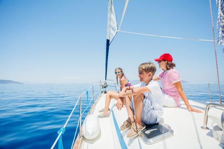 Ragazzo con sua sorella e sua madre a bordo di uno yacht a vela in crociera estiva.