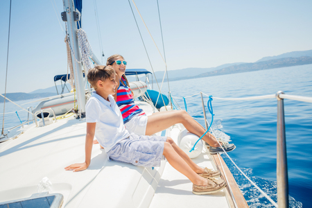 Boy with his sister on board of sailing yacht on summer cruise. Stockfoto