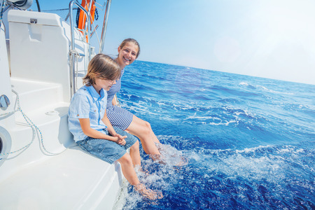 Boy with his sister on board of sailing yacht on summer cruise. Stock fotó