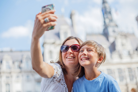 Happy mother and her son making selfie near Hotel de Ville in Paris. Tourists enjoying their vacation in France.