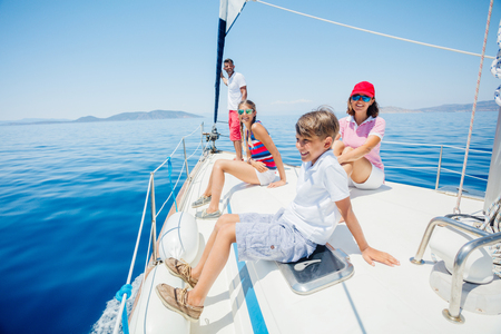 Junge mit seiner Schwester und seiner Mutter an Bord einer Segelyacht auf Sommerkreuzfahrt.