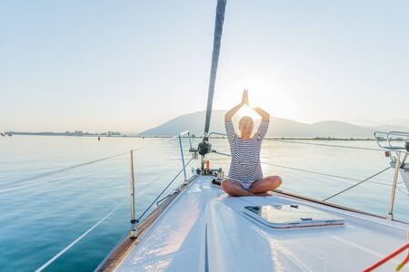 Girl is practicing yoga on the deck of the yacht boat 免版税图像