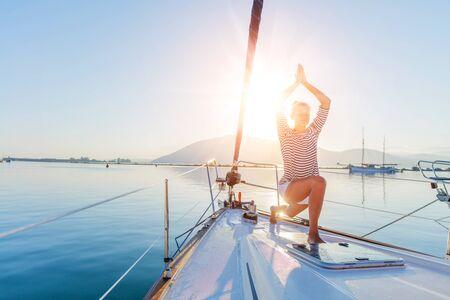 Schön praktiziert Yoga auf dem Deck des Yachtbootes