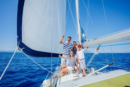 Happy family with adorable daughter and son resting on a big yacht Stock Photo - 137218459