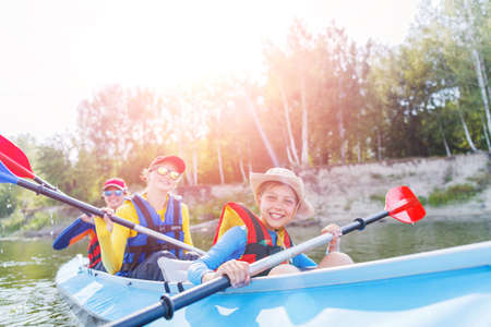 Happy kids kayaking on the river on a sunny day during summer vacation Banco de Imagens