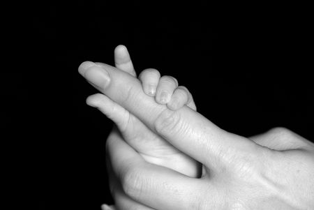 Five week old baby holding mothers finger.