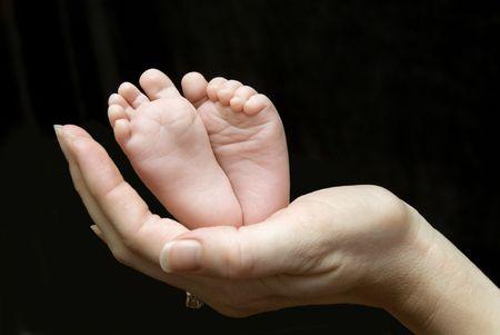 Five week old baby feet held in mothers hand. Banco de Imagens