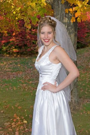 Autumn Bride posing in park near colorful trees.