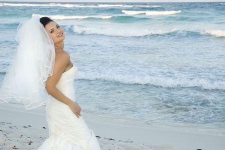 Bride on beach striking a pose.