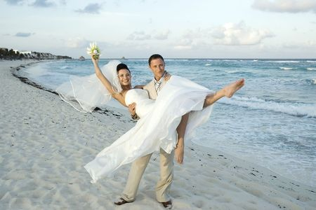 beach wedding: Brige and groom celebrating on the beach