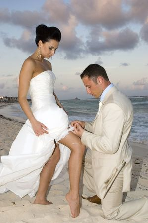 Groom removing the brides garter belt on the beach. Stock Photo - 2433638