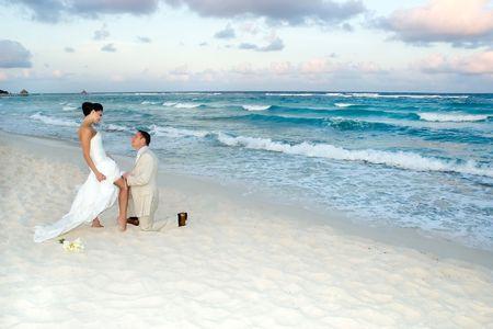Groom removing the brides garter belt on the beach.