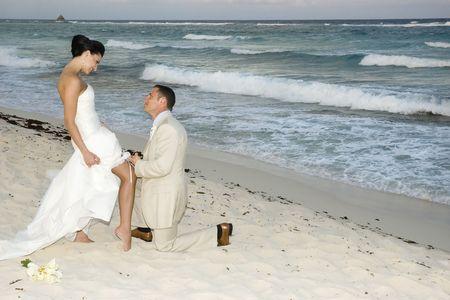 serf: Groom enlever la ceinture de la mari�e jarreti�re sur la plage.