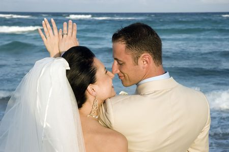 Bride and Groom looking that their rings on the beach.