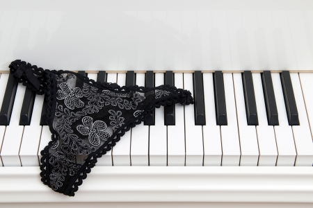 white panties: Pair of ladies lace panties on the keyboard of a white  grand piano.