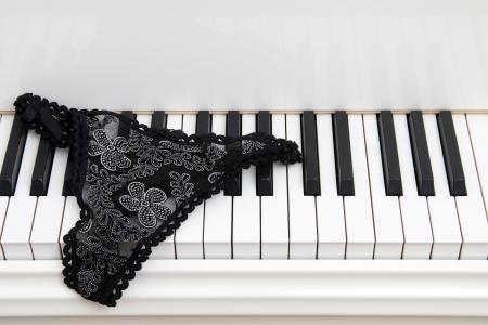 panties: Par de se�oras bragas de encaje en el teclado de un piano de cola blanco.
