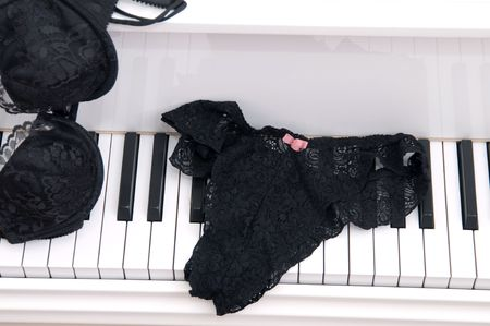 Set of ladies lace lingerie on the keyboard of a white  grand piano. 版權商用圖片