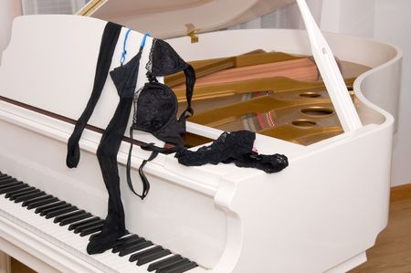 Set of ladies lace lingerie on the keyboard of a white  grand piano. Banco de Imagens