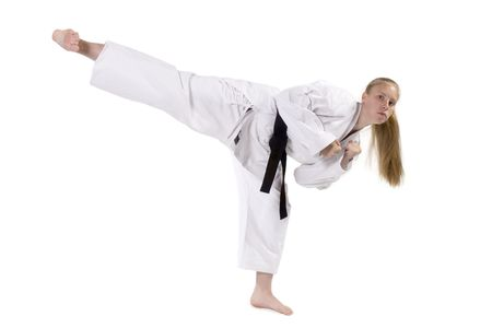 martial arts woman: Female Third Degree Black Belt throwing a side kick.