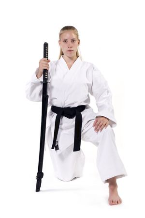 Female Third Degree Black Belt kneeling with katana. Stok Fotoğraf