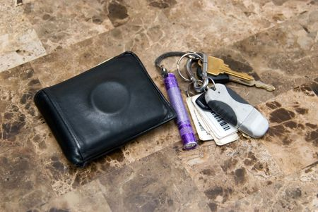 Mens wallet with condom ring and car keys.
