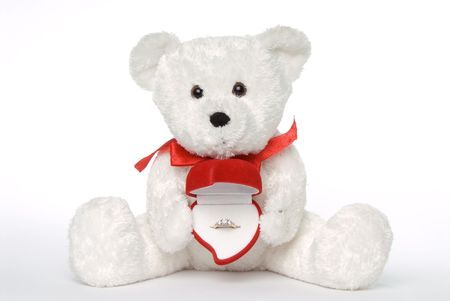 White teddy bear with engagement ring in heart shaped ring box