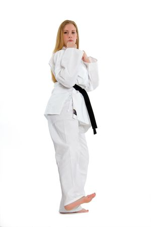 Black belt female martial artist doing low side kick photo