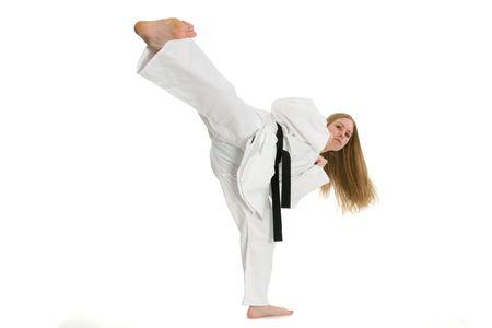 taekwondo: Black belt female martial artist doing side kick.