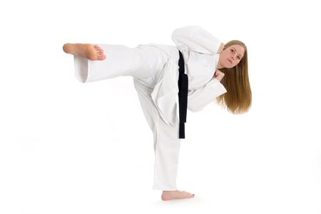 Black belt female martial artist doing side kick.