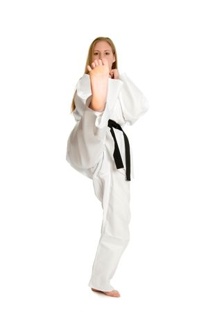 martial artist: Black belt female martial artist doing front kick.