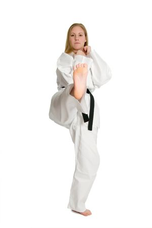 Black belt female martial artist doing front kick.