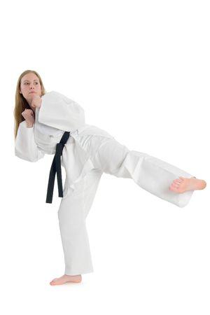 Black belt female martial artist doing side kick.