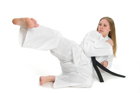martial arts woman: Black belt female martial artist doing kick on the ground.