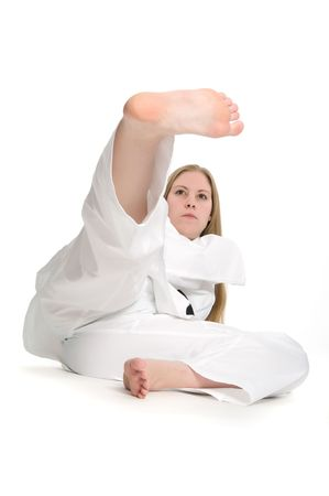 Black belt female martial artist doing kick on the ground.