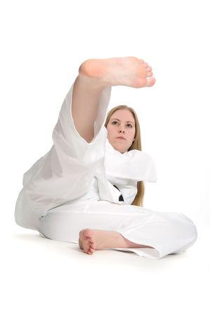 taekwondo: Black belt female martial artist doing kick on the ground.