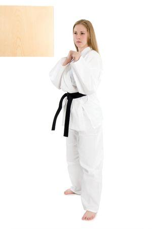 Black belt female martial artist doing board break. Banco de Imagens