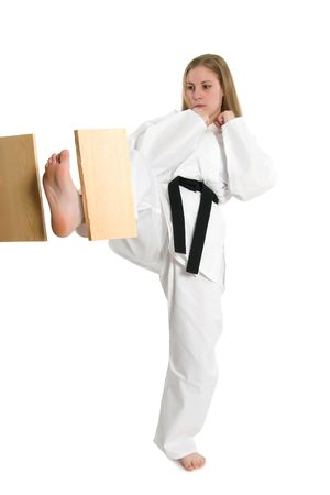 Black belt female martial artist doing board break. Imagens