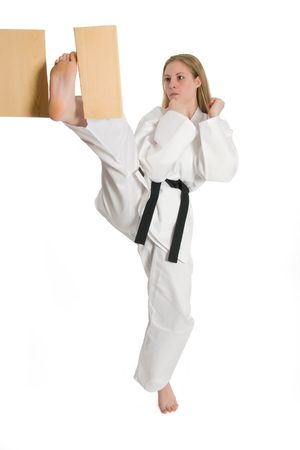 Black belt female martial artist doing board break. Stock Photo