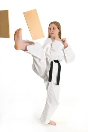Black belt female martial artist doing board break. Banco de Imagens