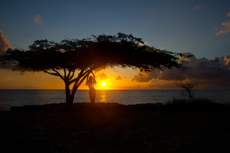 Woman by tree at sunset in Aruba